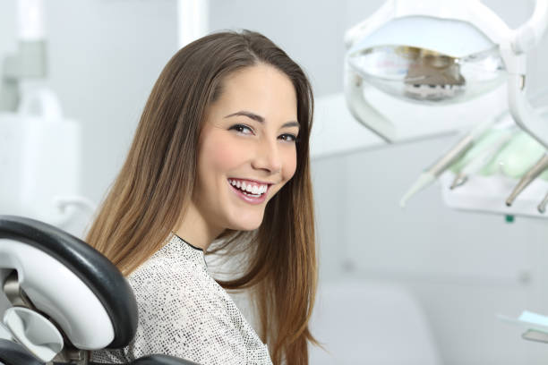 Dentist patient showing perfect smile after treatment Satisfied dentist patient showing her perfect smile after treatment in a clinic box with medical equipment in the background dental health stock pictures, royalty-free photos & images