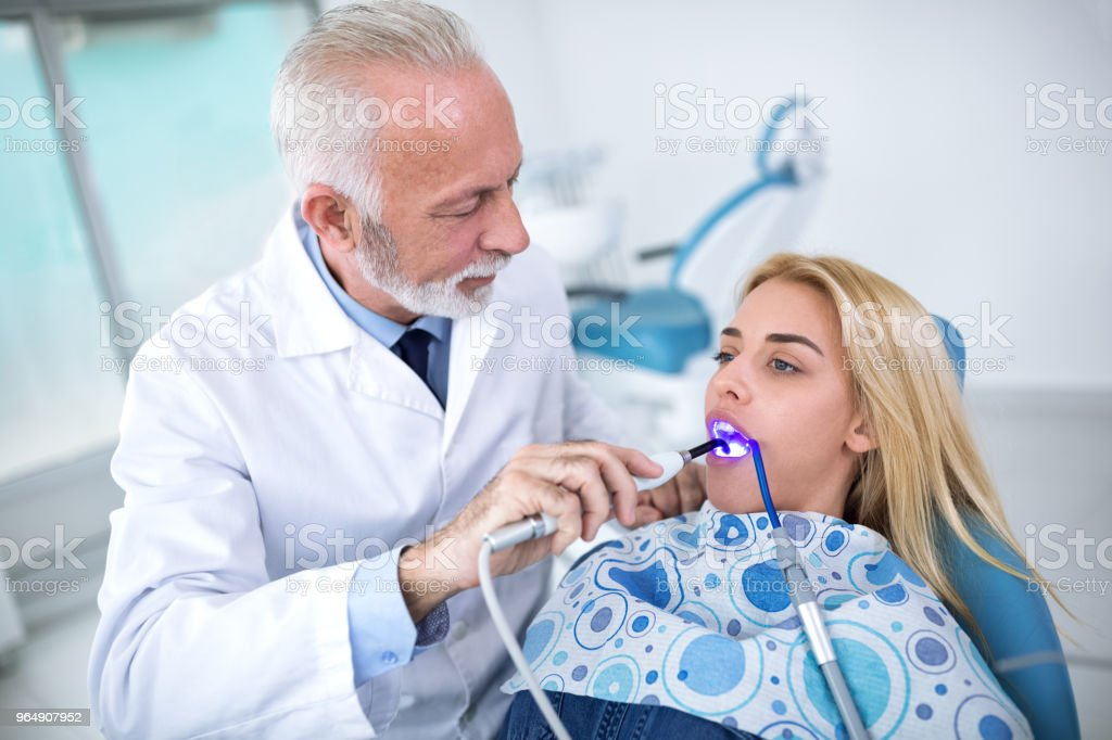 Dentist plumbing teeth to young woman royalty-free stock photo