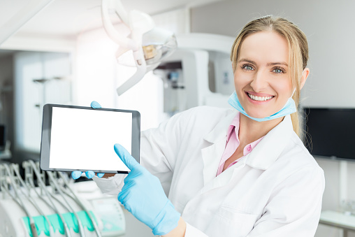 928855610 istock photo Dentist pointing tablet with blank screen 652641384