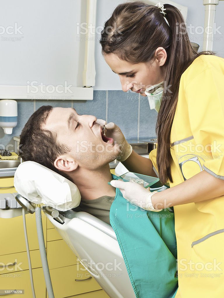 Dentist puts the remedy in patients tooth royalty-free stock photo