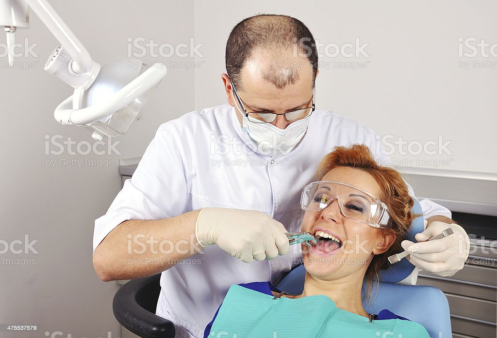 dentist removes tooth stock photo
