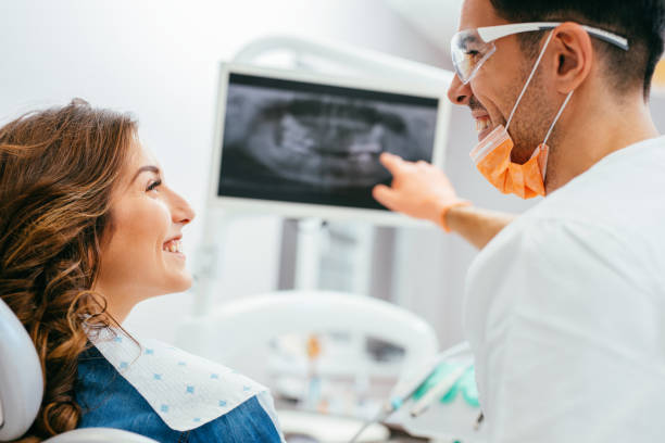 dentist showing a patient her x-ray - medical x ray stock pictures, royalty-free photos & images