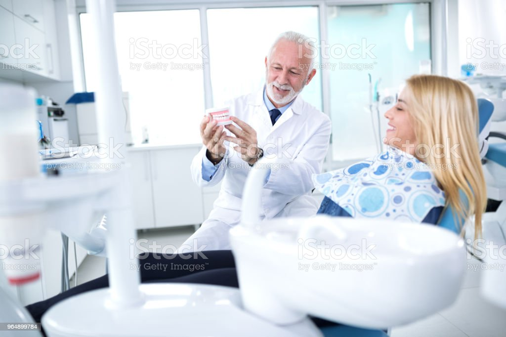 Dentist showing patient how teeth will look after treatment royalty-free stock photo