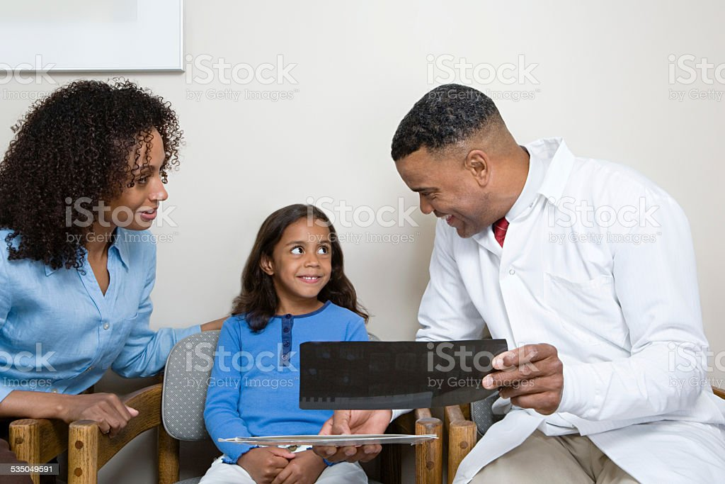 Dentist showing patient x ray stock photo