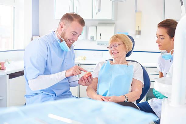 dentist showing senior patient model of dentures - Photo