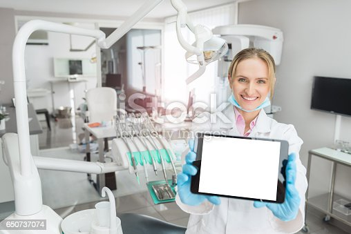 863476166istockphoto Dentist showing tablet with blank screen 650737074