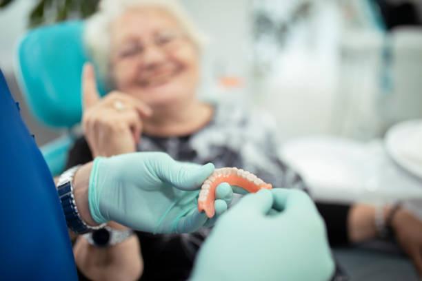 zahnarzt zeigt einem patienten zahnprothesen - menschlicher zahn stock-fotos und bilder