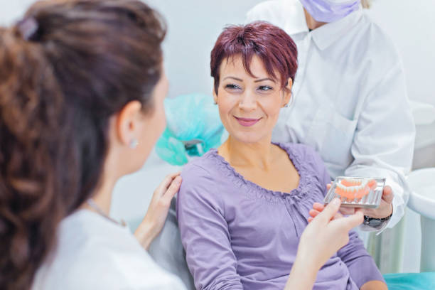 dentist showing teeth dentures to a patient - dental implants stock photos and pictures