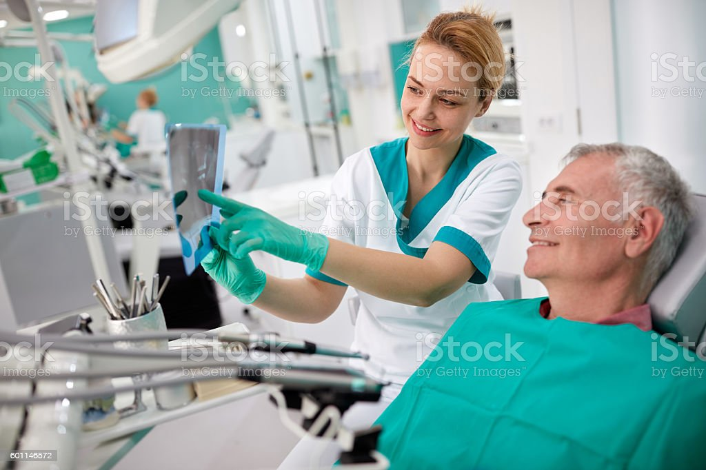 Dentist showing teeth problem on dental X-ray stock photo