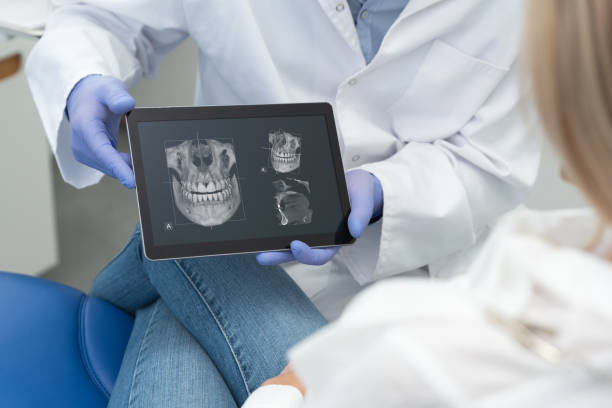 Dentist showing teeth x-ray on tablet screen stock photo
