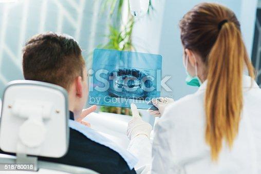 istock Dentist showing to patient roentgen. 518780018