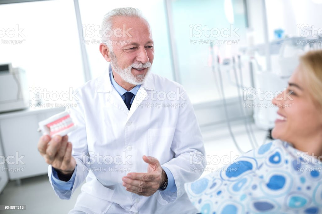 Dentist shows the patient the results of prosthetics royalty-free stock photo