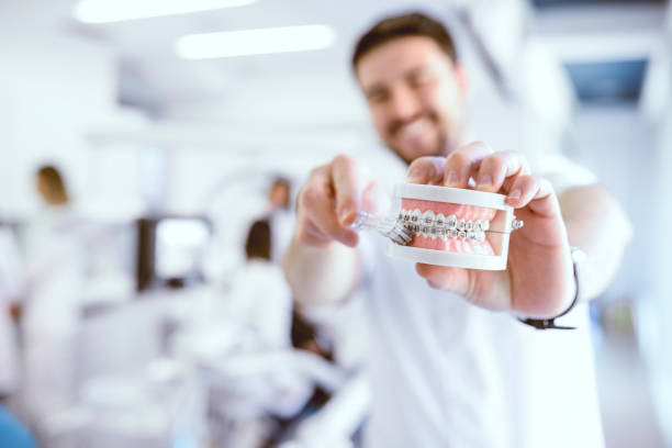 Dentist Shows the Wright Way To Brush Your Teeth with Braces stock photo