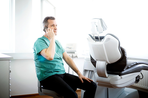 Dentist Talking On Phone While Sitting In Clinic Stockfoto und mehr Bilder von Am Telefon