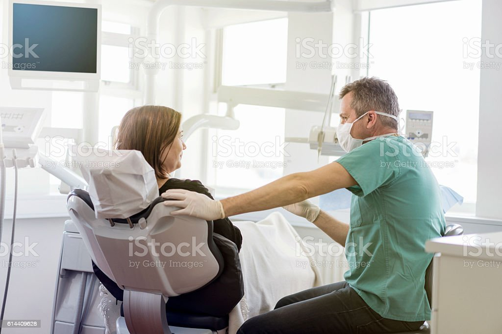 Dentist talking to female patient in clinic stock photo