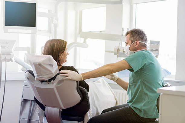 dentist talking to female patient in clinic - two dentists talking bildbanksfoton och bilder