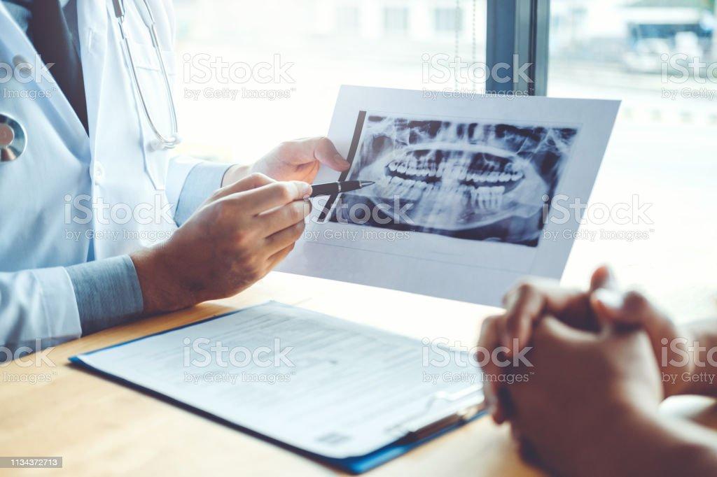 Zahnarzt im Gespräch mit männlichen Patienten und Präsentation der Ergebnisse auf Zahnerl-Röntgenfilm Über das Problem des Patienten in der Zahnarztpraxis - Lizenzfrei Arzt Stock-Foto