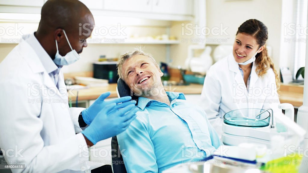 Dentist talking to patient who smiles back as assistant watches stock photo