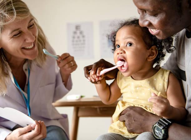 dentist teaching a little girl how to brush her teeth - dentist zdjęcia i obrazy z banku zdjęć
