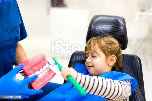 Dentist teaching cute girl about oral hygiene