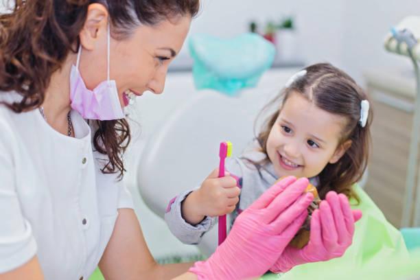 かわいい女の子の口腔衛生についての指導歯科医 - 歯科医師 ストックフォトと画像