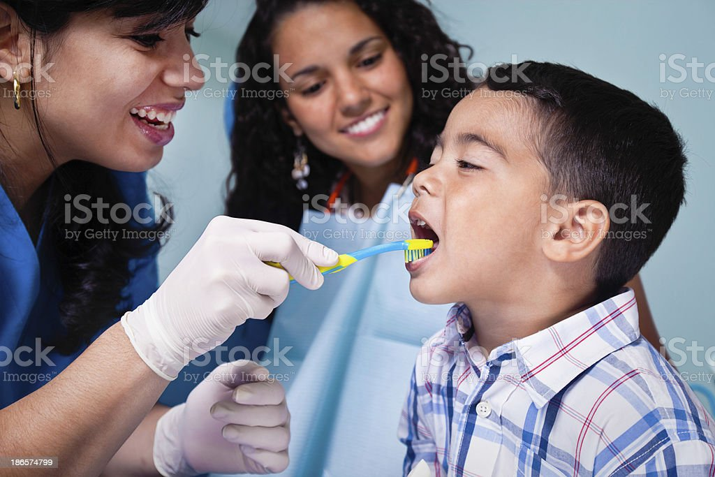 Dentist teaching toothbrush use to child patient stock photo