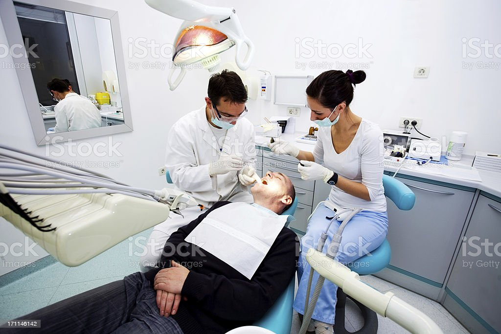 Dentist team and middle aged patient. royalty-free stock photo