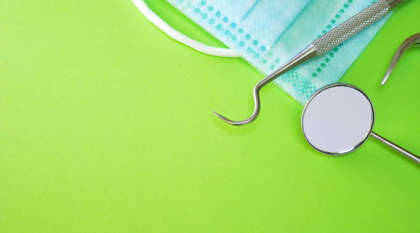 zahnarztwerkzeuge oder instrumente in der zahnarztpraxis: zahnkundlicher forscher, sichelsonde, zahnspiegel und chirurgie oder prozedur-gesichtsmaske auf grünem hintergrund. zahnhygiene und gesundheitskonzeptionelles image - sprechstundenhilfe stock-fotos und bilder