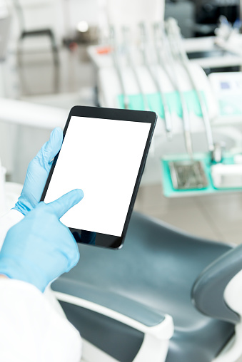 928855610 istock photo Dentist touching blank screen tablet 657533604