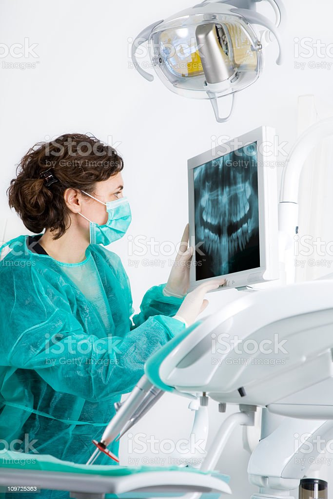A dentist using an X-ray image to diagnose a patient stock photo