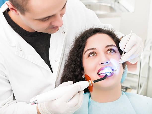 Dentist using dental curing UV lamp stock photo