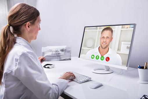 Dentista Videoconferencia Con Hombre En Computadora Foto de stock y más banco de imágenes de Adulto - iStock