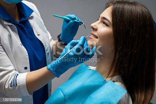 istock dentist wearing blue gloves examines smiling woman patient using dental scaler while she is sitting half a turn in dental chair in clinic , healthcare concept 1207033255