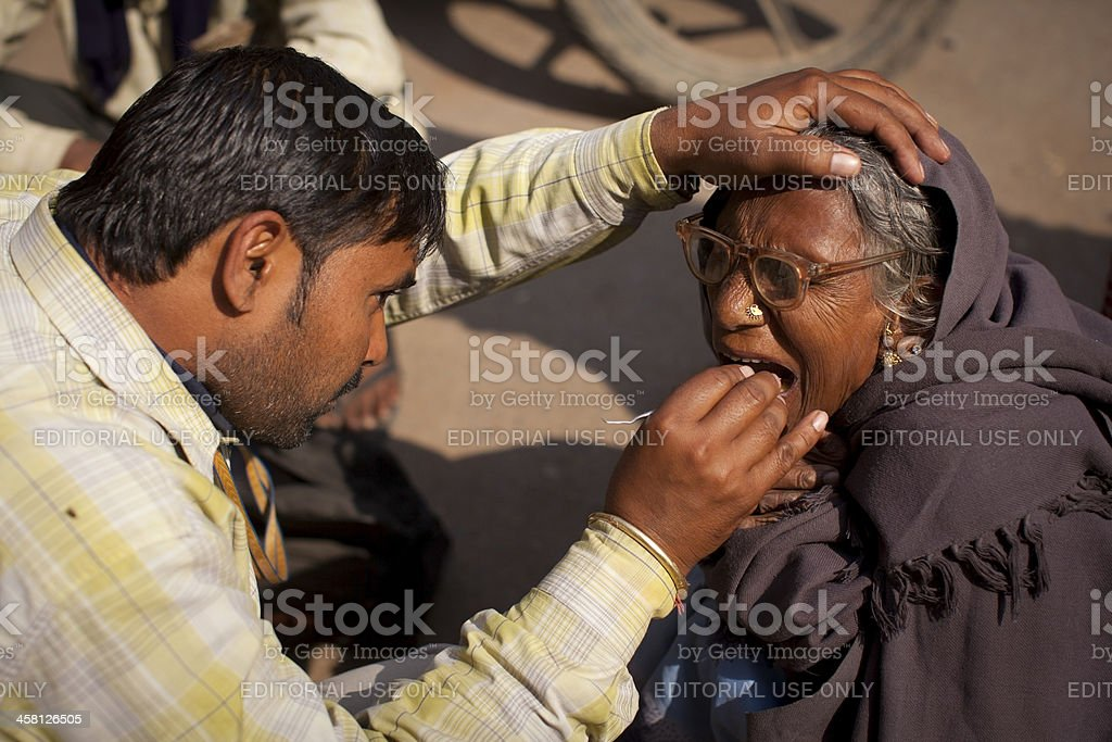 Dentist with a woman patient at the roadside, India stock photo