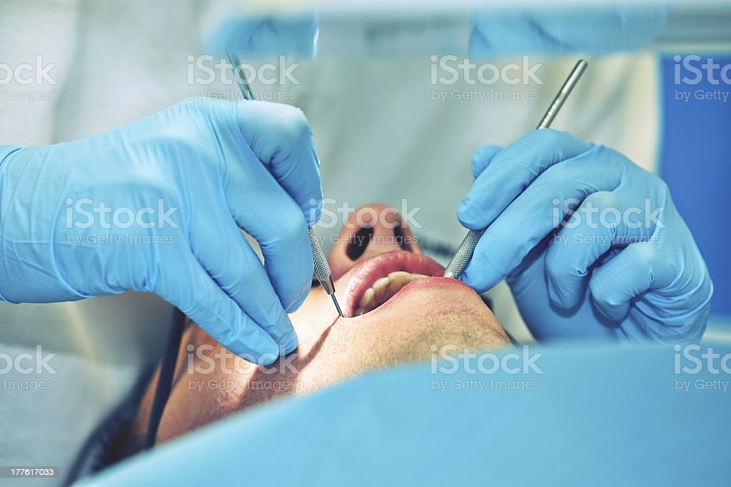Dentist with blue gloves examining a patient stock photo