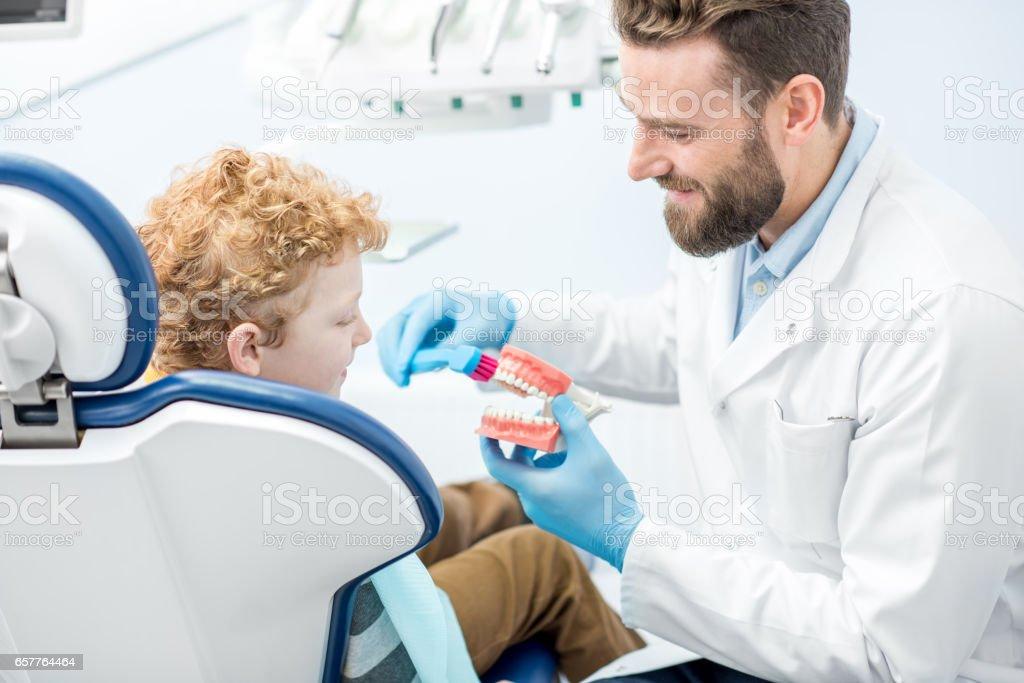 Dentista con el niño en el consultorio dental - foto de stock