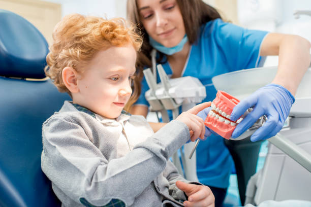 Dentist with boy at the dental office stock photo