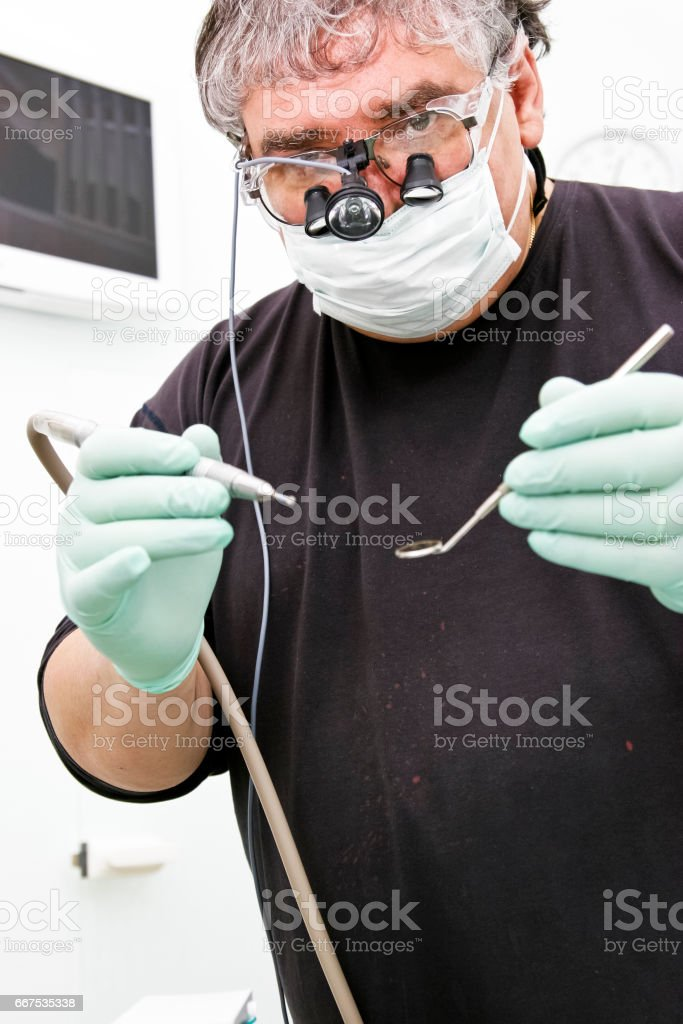 Dentist with special eyeglass a drill and angled mirror foto stock royalty-free