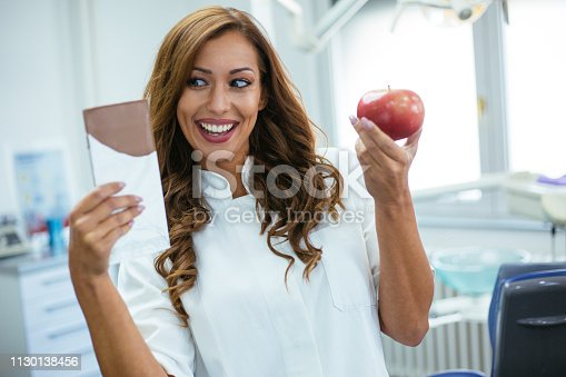 Female dentist making choice between apple and chocolate