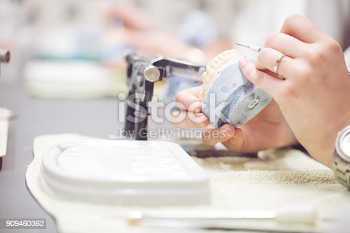 istock Dentist working on set of teeth 909460362