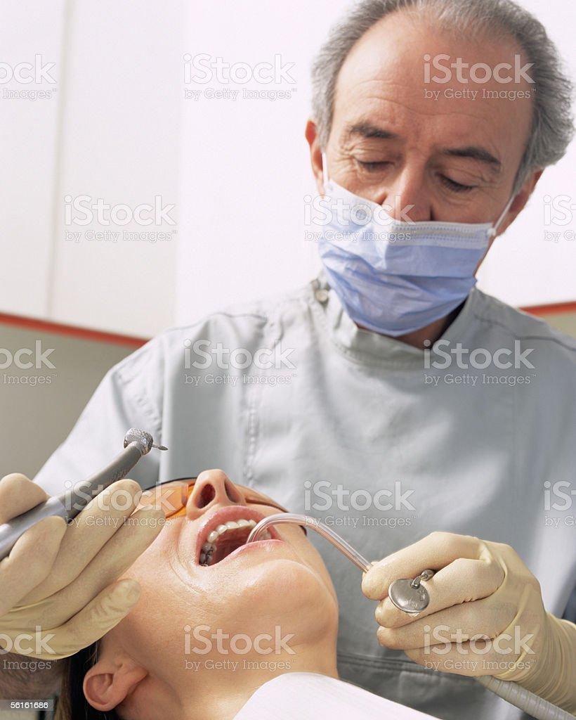 Dentist working on woman's teeth stock photo