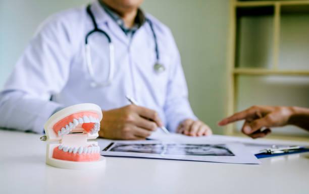 zahnärzte sind zahnprobleme bei bericht röntgenbild patienten diskutiert. - zahnimplantat stock-fotos und bilder