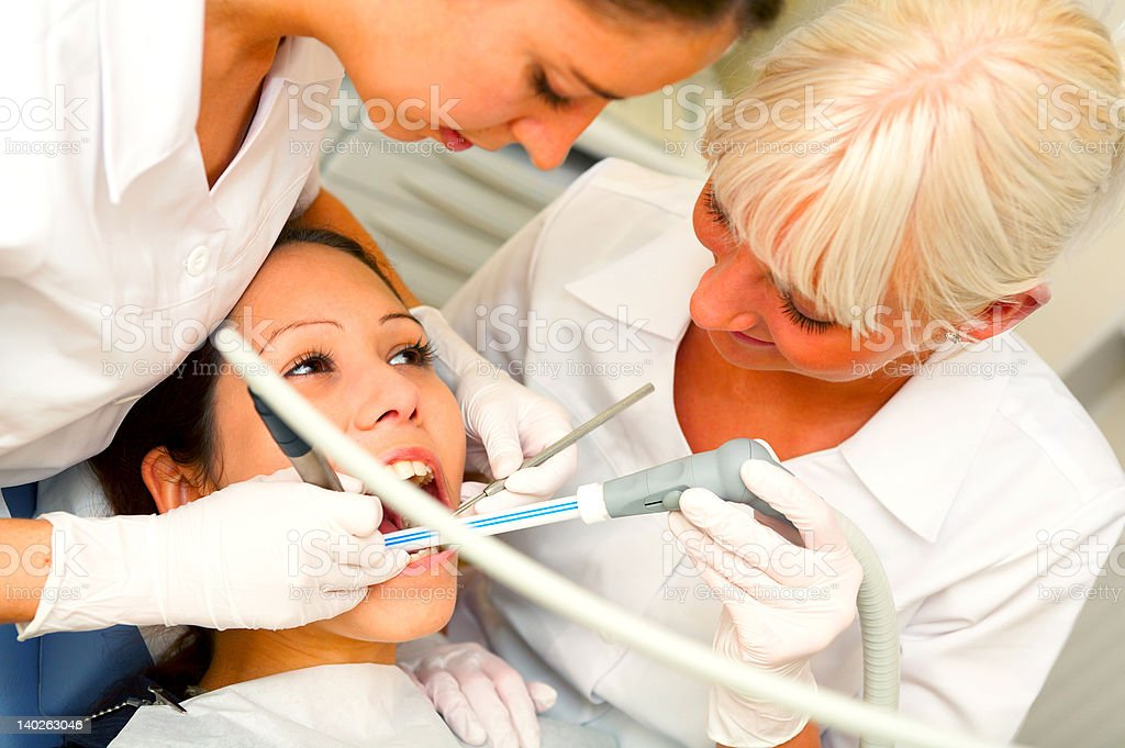 Dentists assisting a female patient.