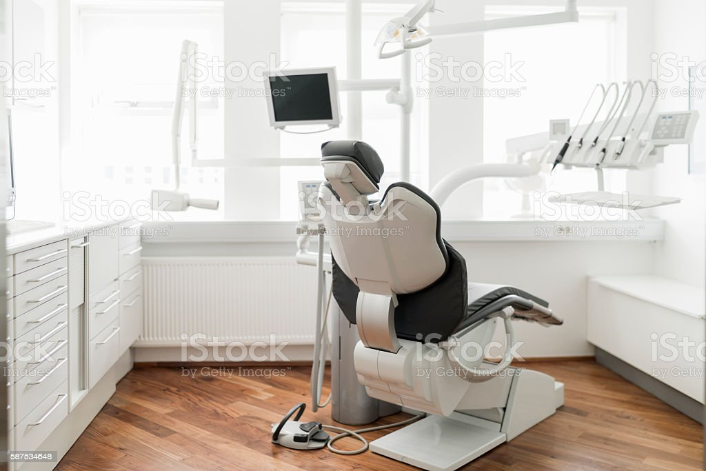 Dentist's chair in brightly lit clinic stock photo