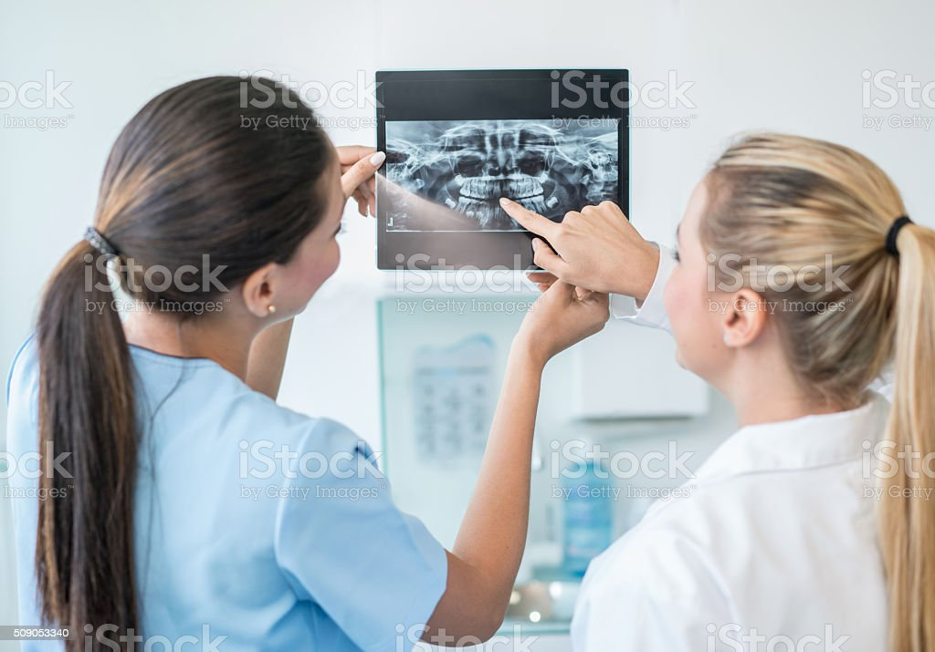 Dentists looking at tooth x-ray stock photo