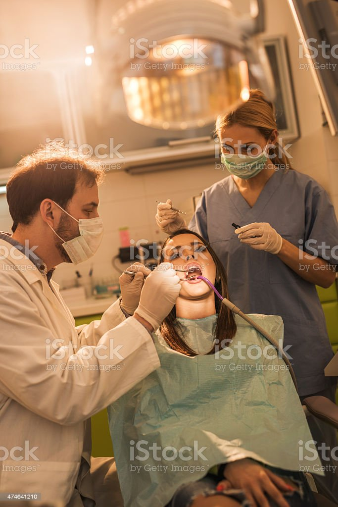 Two dentists doing dental filling procedure on young woman.