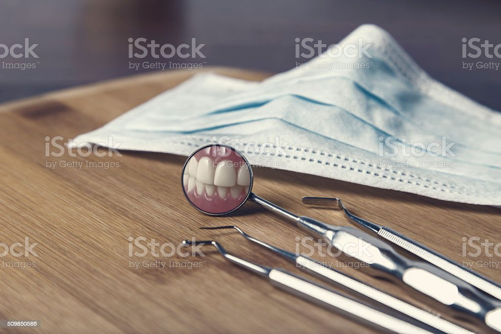 dentists tools and mask with reflection of teeth stock photo more