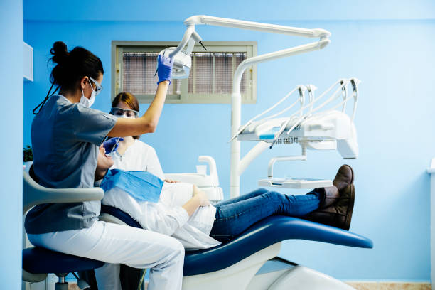 Dentists with a patient during a dental intervention. stock photo