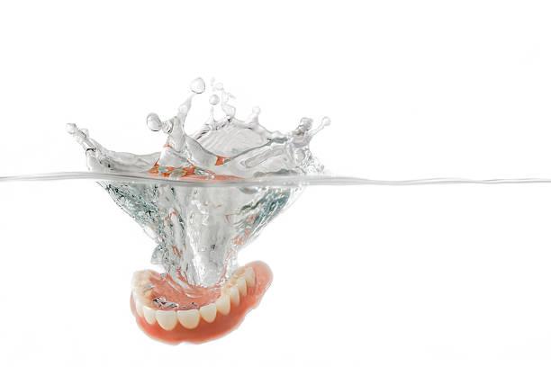 dentures splashing into clear water - tandprotes människotänder bildbanksfoton och bilder