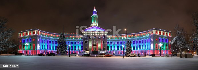 The Denver City and County Building, shown here illuminated for the holiday seasons with snow in the foreground.